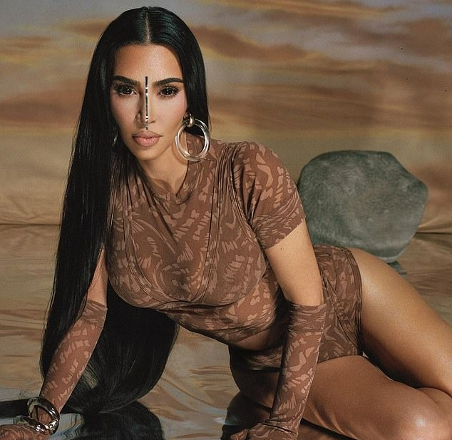 Kim Kardashian wearing a figure hugging brown tee with a mesh material, short sleeves, brand logo and a mock neck