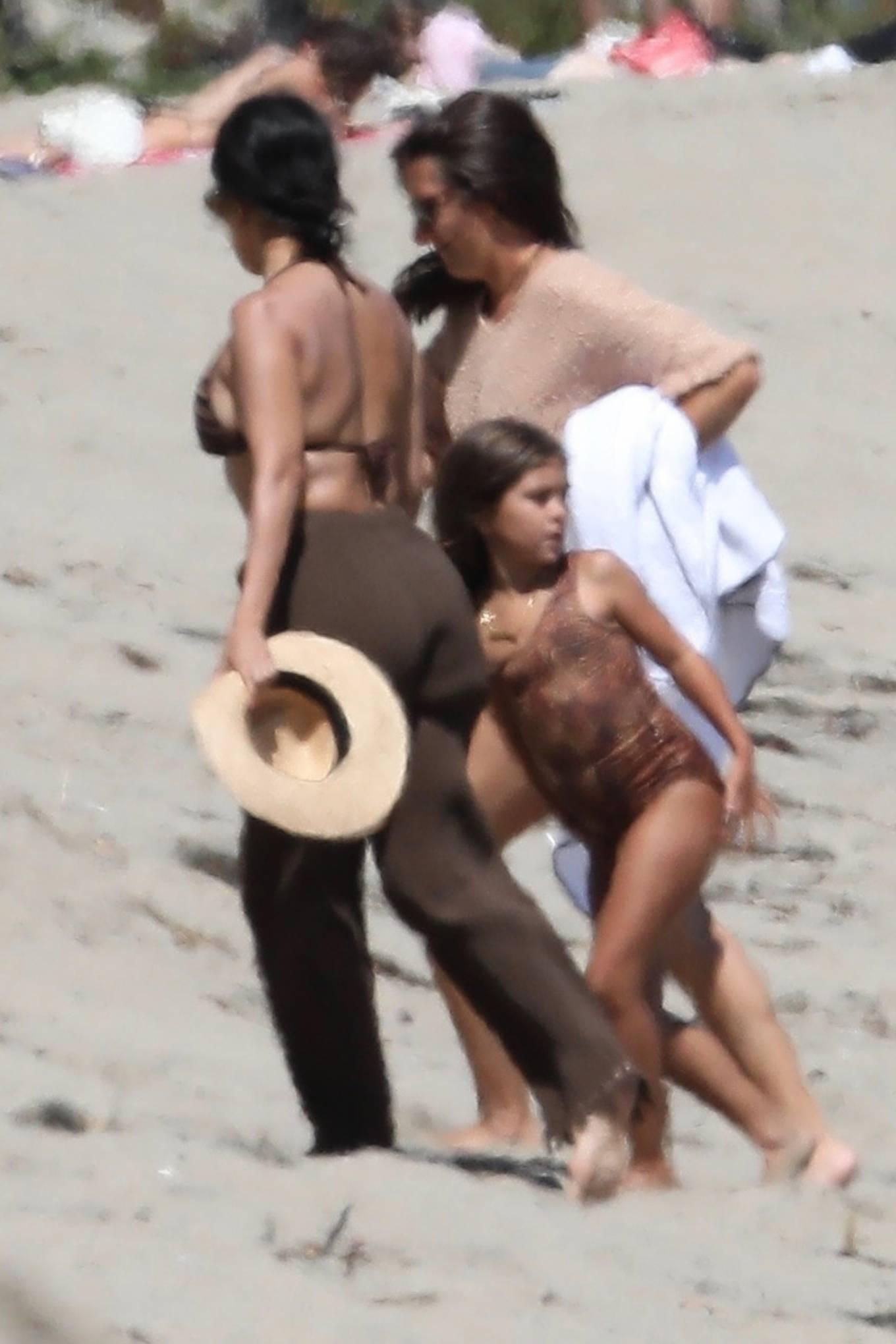 Kourtney Kardashian wearing straight fit brown high waist trousers