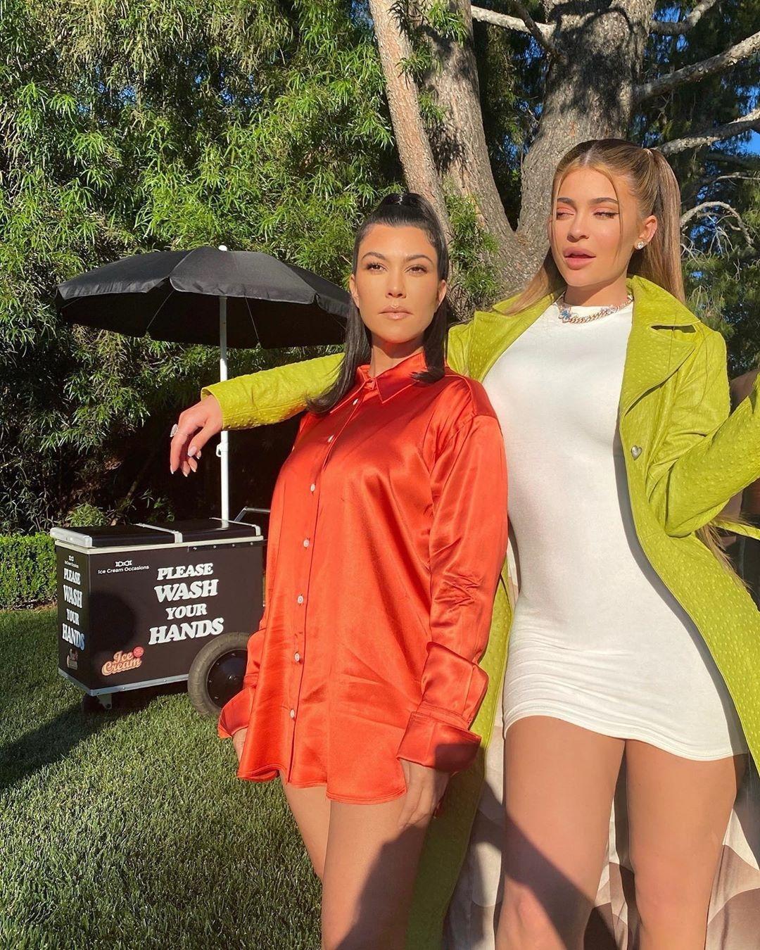Kourtney Kardashian rocking a Oversized shiny burnt orange shirt with a satin fabric, extra long sleeves, shirt collar, button front and curved hem