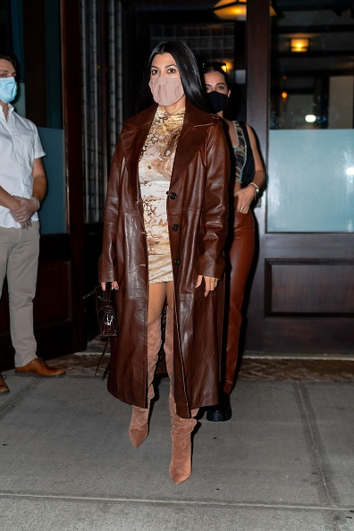 Kourtney Kardashian donning pointy tan suede knee high boots with high heel