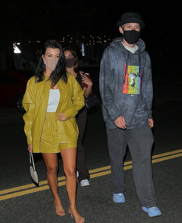 Kourtney Kardashian donning see-through brown v-strap sandals with pointy heel and strappy