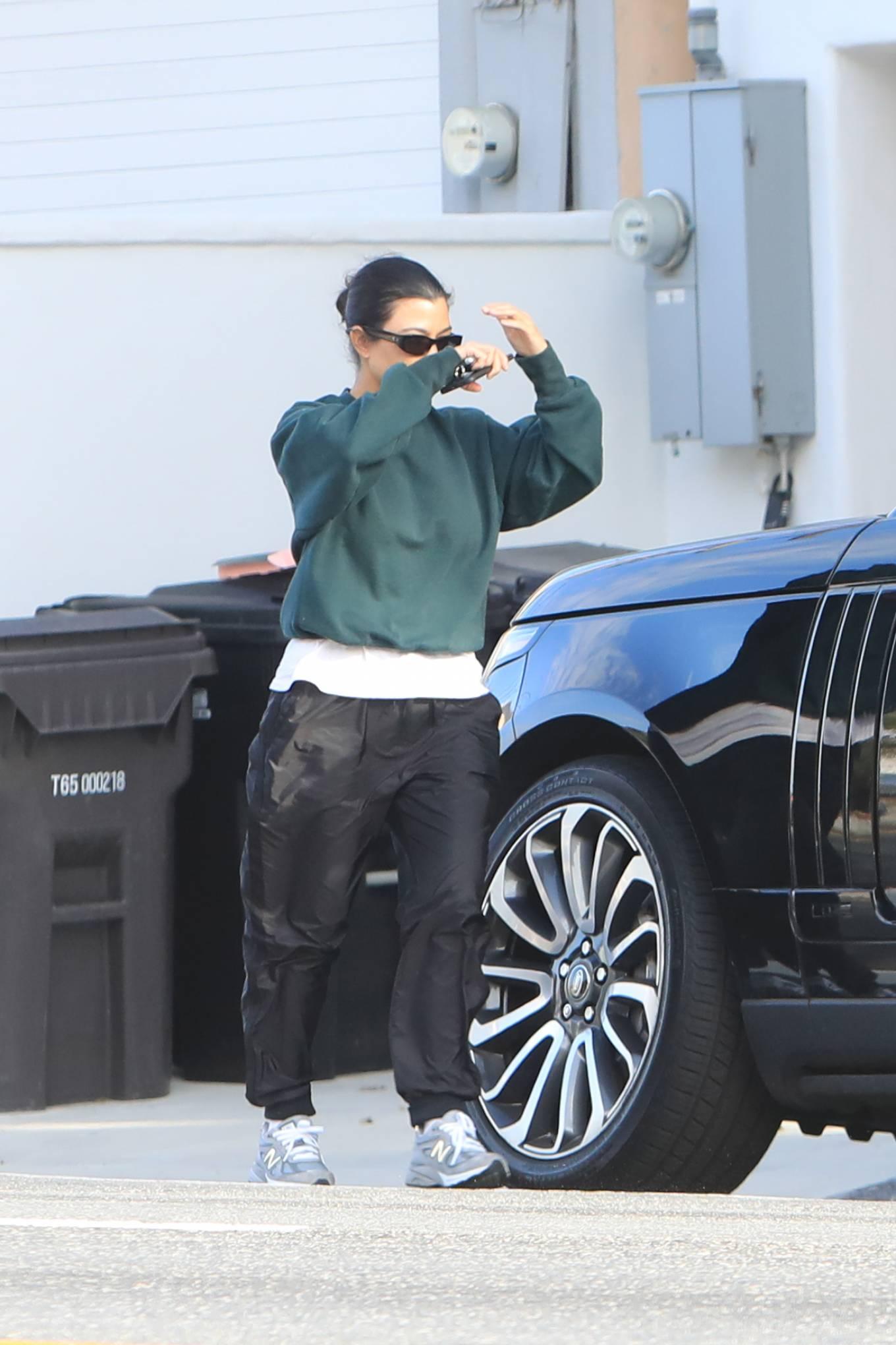 Kourtney Kardashian rocking brand logo grey mesh lace-up sneakers by New Balance