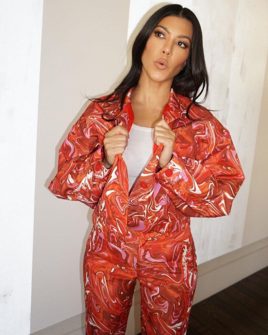 Kourtney Kardashian, white boots, orange crop jacket, high heel, narrow, pointy, white tank top, orange trousers. Kourtney Kardashian rocking pointy white boots with high heel