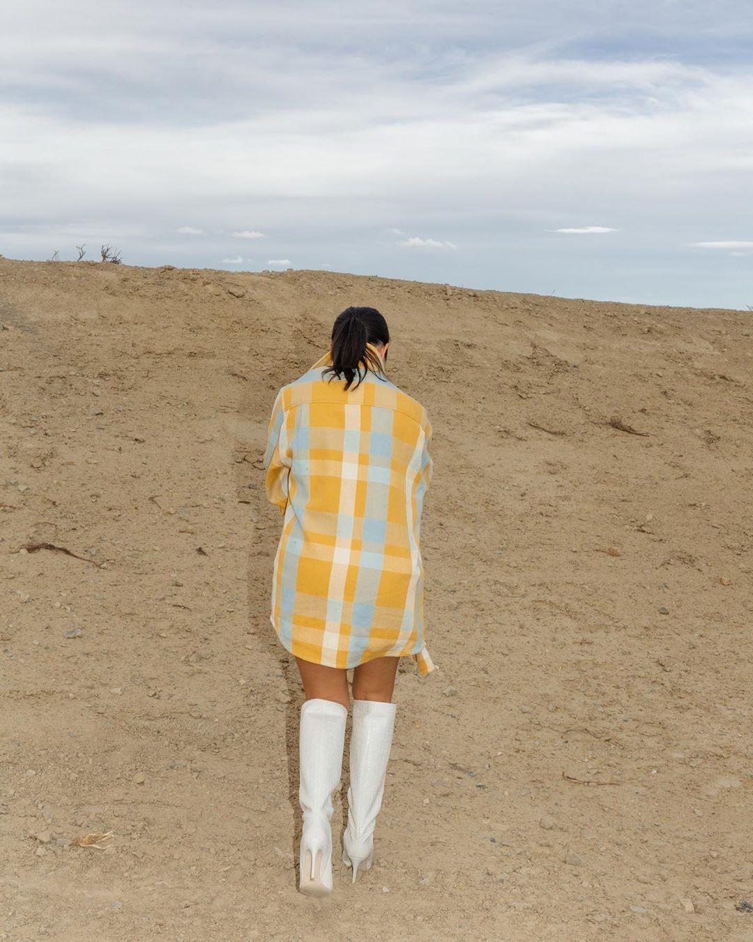 Kourtney Kardashian donning a oversized yellow checks shirt with extra long sleeves and shirt collar