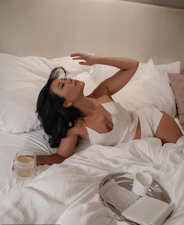 Kourtney Kardashian donning Sexy white satin shorts with a satin material
