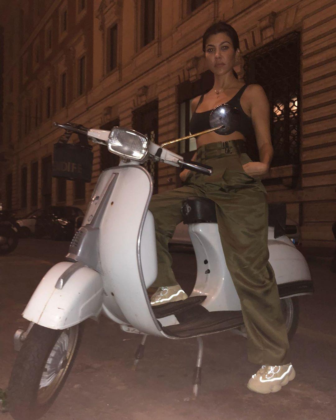 Kourtney Kardashian donning round white leather lace-up sneakers