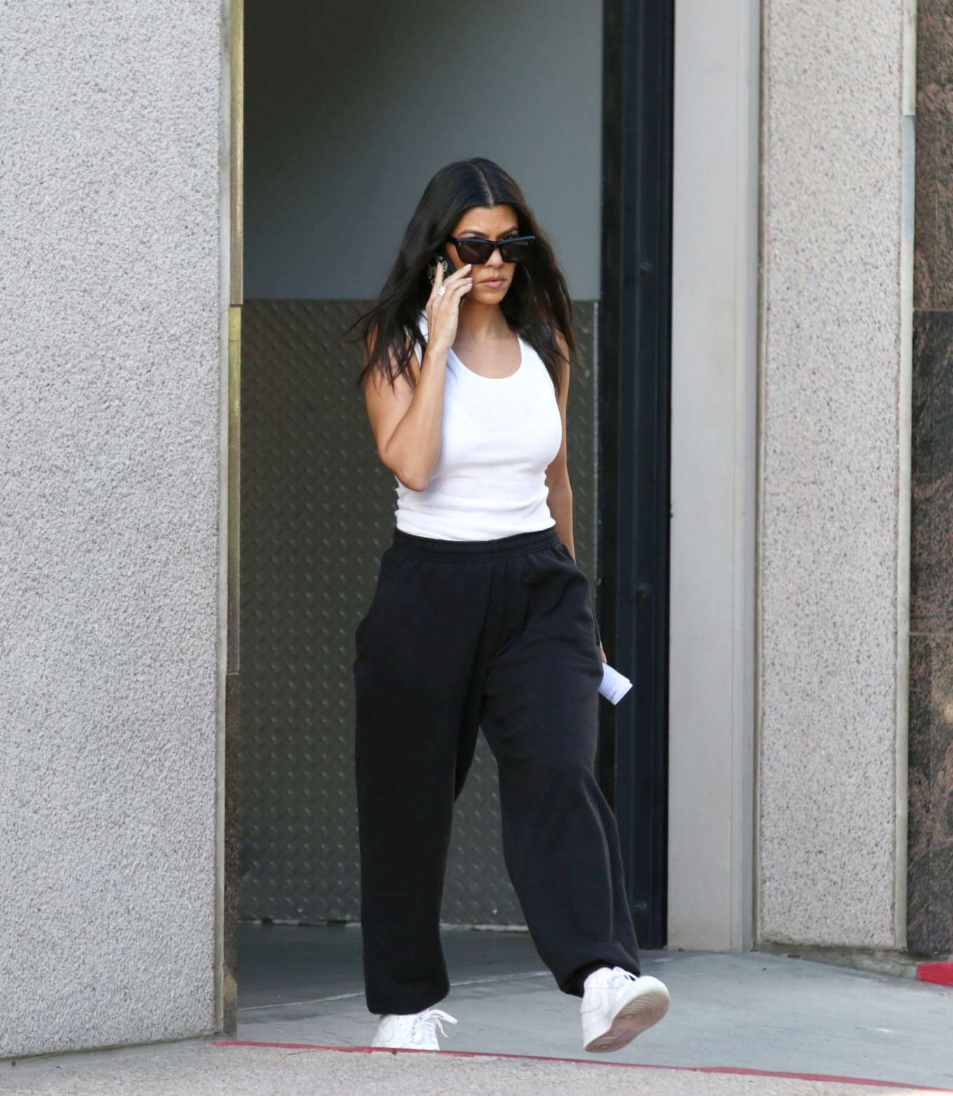 Kourtney Kardashian rocking black baggy sweatpants with side pockets