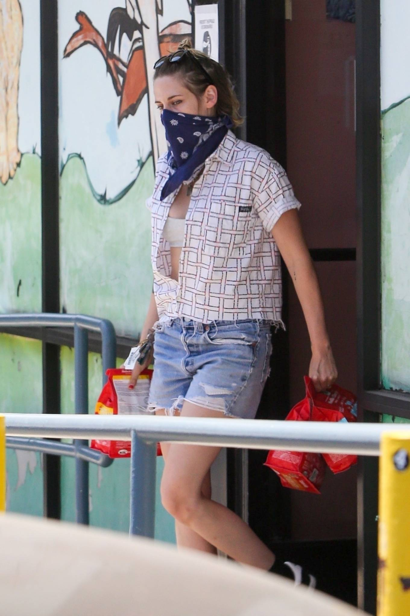 Kristen Stewart donning a White tucked in shirt with rolled sleeves, shirt collar and pattern