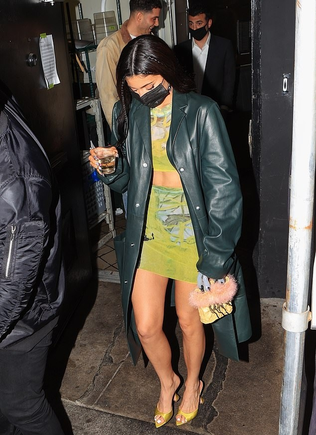 Kylie Jenner wearing a oversized dark green open front leather trench coat with full sleeves, lapel collar and button front