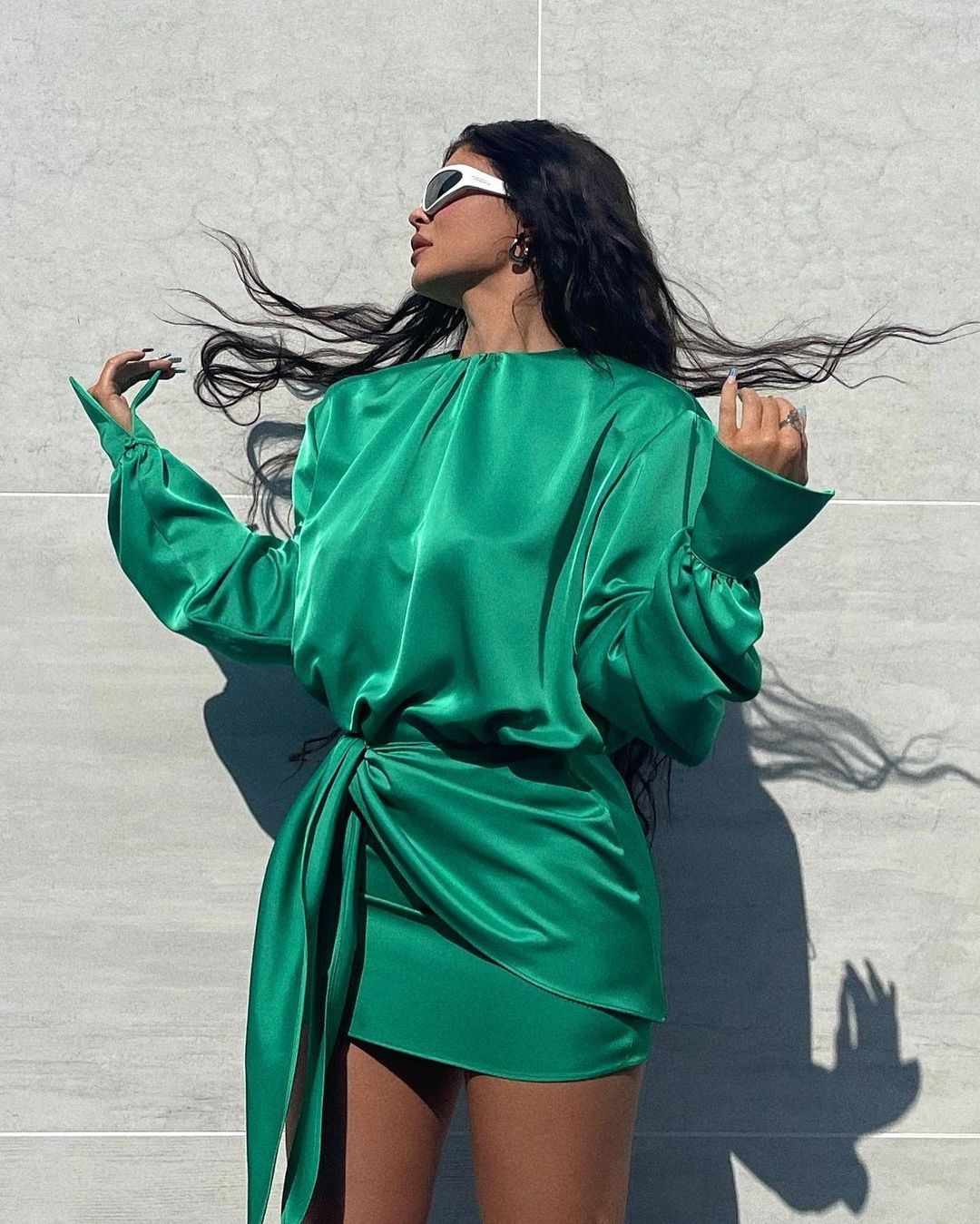 Kylie Jenner donning a Shiny green Attico crepe draped mini dress with a satin fabric, extra long sleeves, asymmetric design, a high neck and asymmetric hem