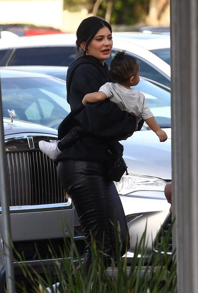 Kylie Jenner donning high rise black leather ankle length jeans