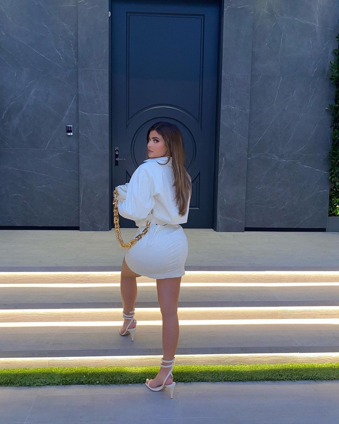 Kylie Jenner wearing a Oversized white leather mini shirt dress with a leather material, extra long sleeves and shirt collar