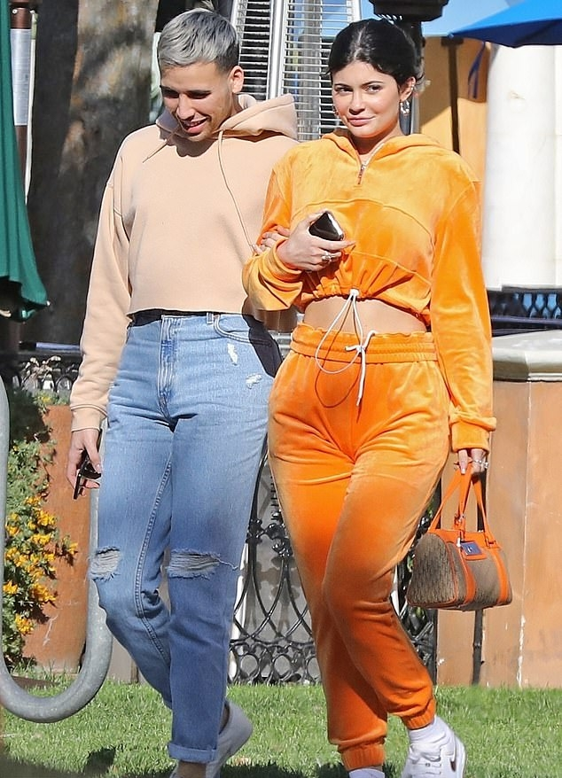 Kylie Jenner wearing a Oversized Bright yellow velvet hoodie with a velvet fabric, extra long sleeves, elastic drawstring hem and gathered hem