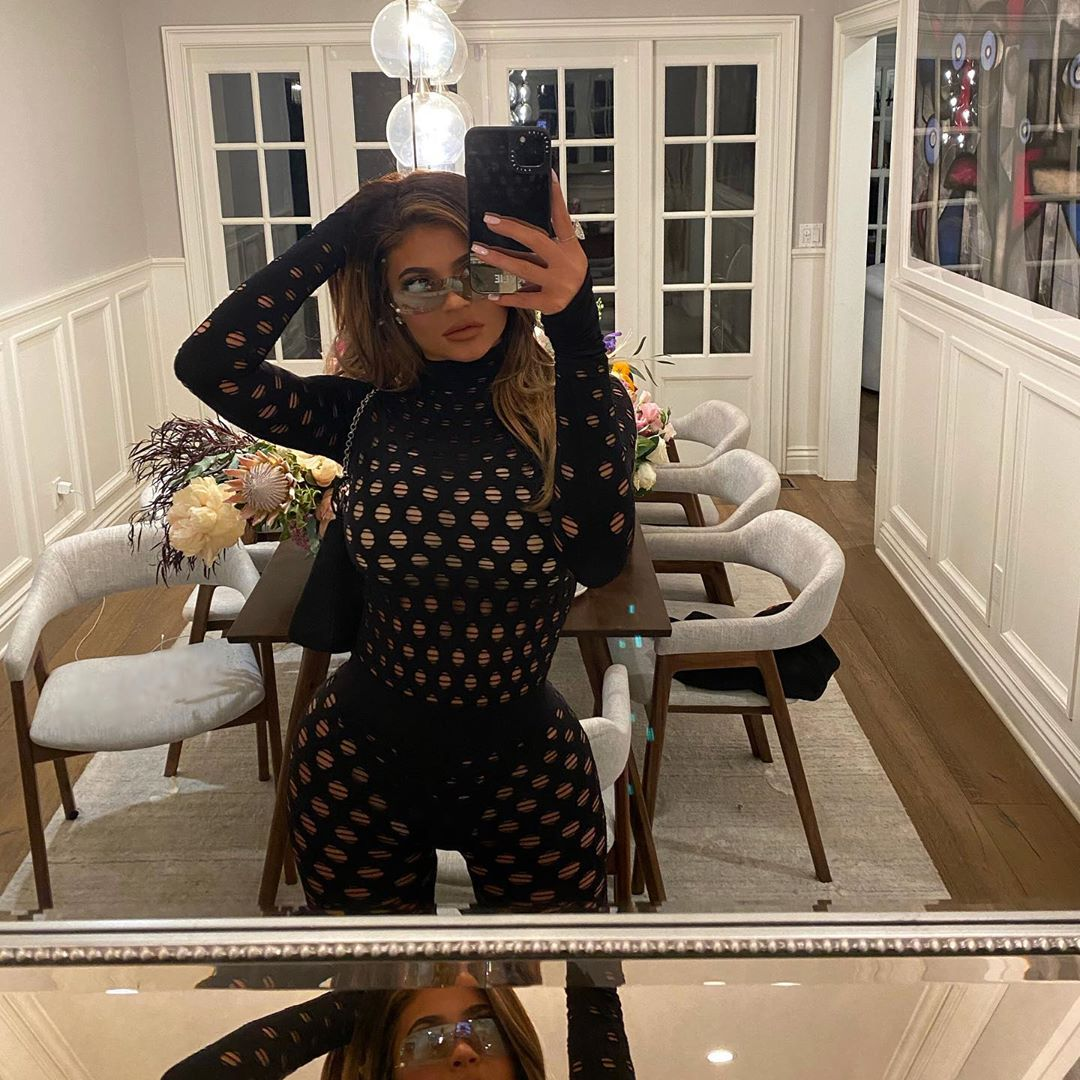 Kylie Jenner rocking a Figure hugging black Maisie Wilen cut out bodysuit with extra long sleeves, cut out and a turtleneck
