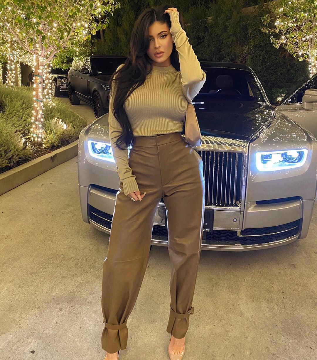 Kylie Jenner wearing Straight fit dark leaf green leather trousers with a leather material