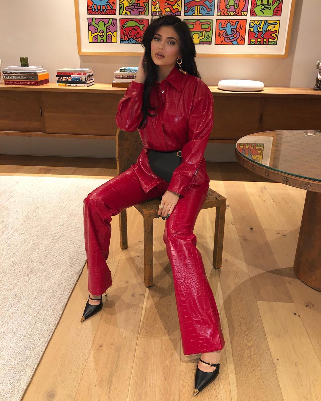 Kylie Jenner wearing straight fit bright deep red leather trousers with a snakeskin material