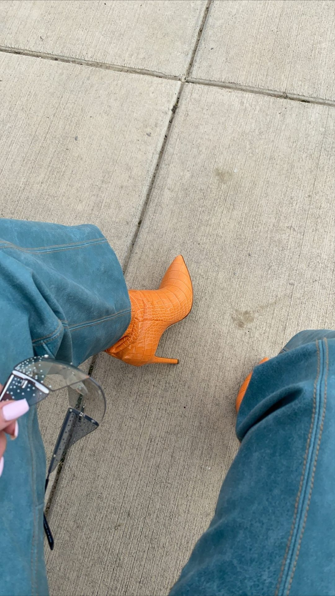 Kylie Jenner wearing narrow orange leather boots with ice pick heel