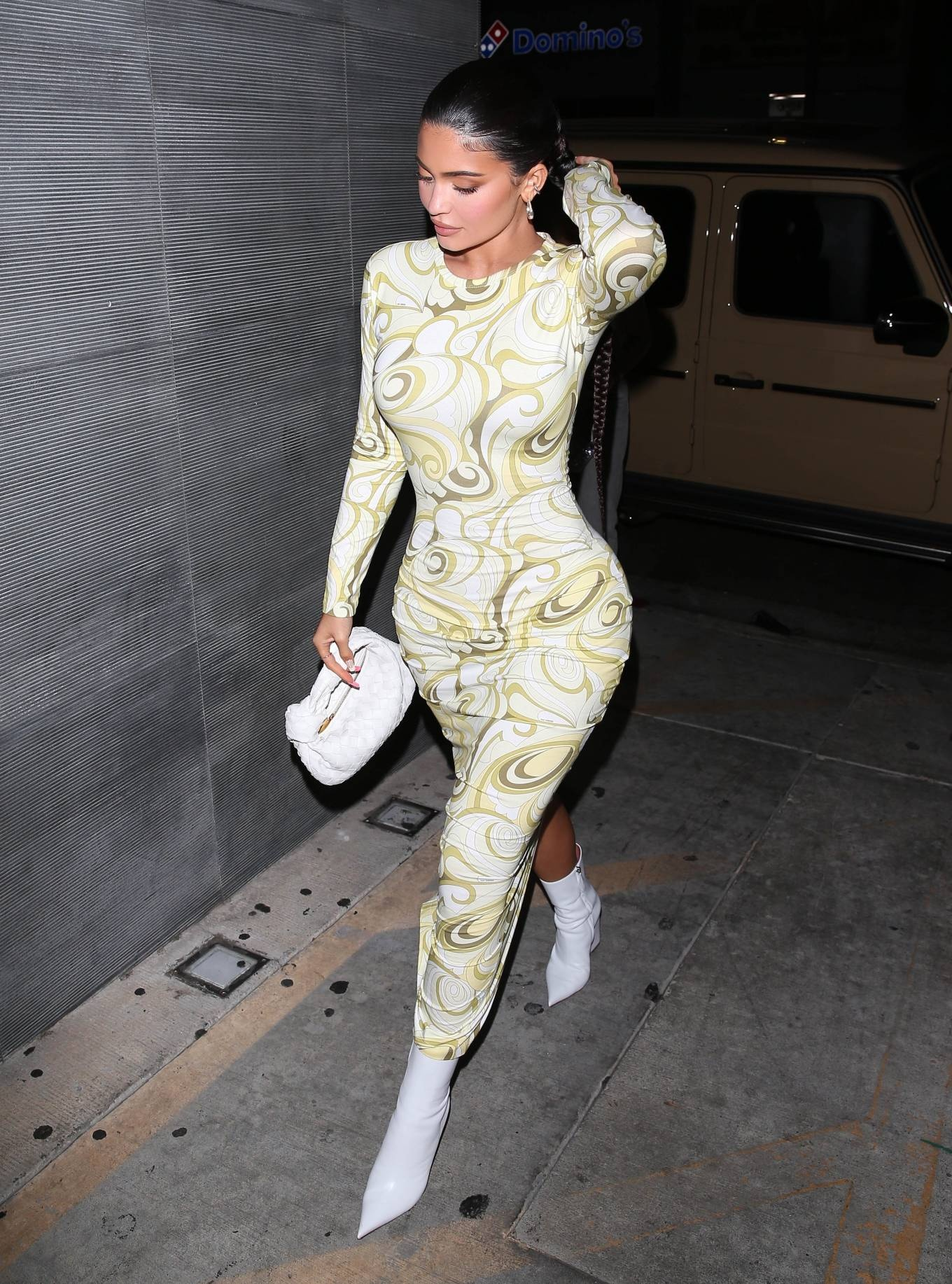 Kylie Jenner donning pointed white leather ankle boots by Amina Muaddi with platform heels
