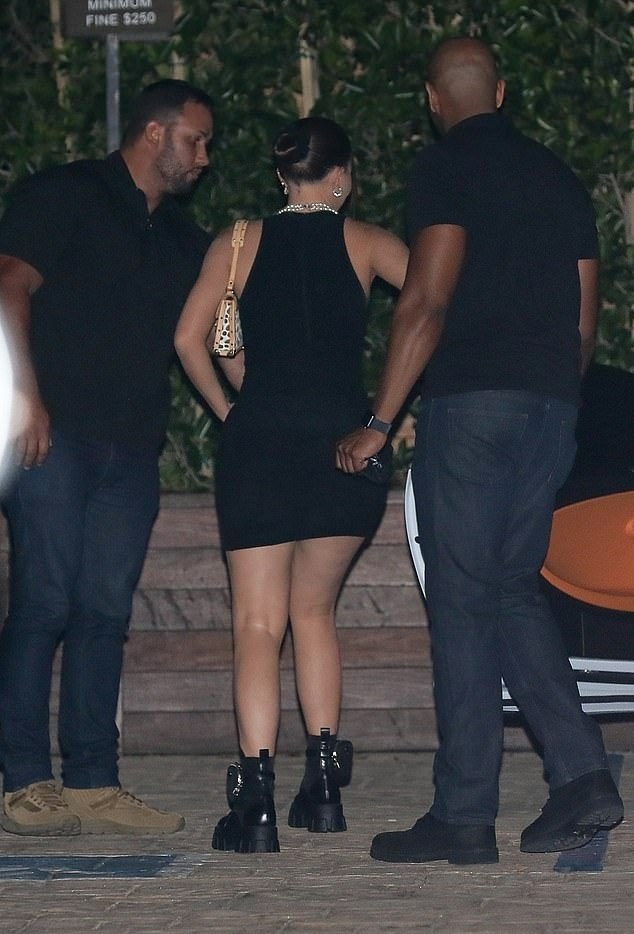 Kylie Jenner wearing a formfitting black dress with a halter neck