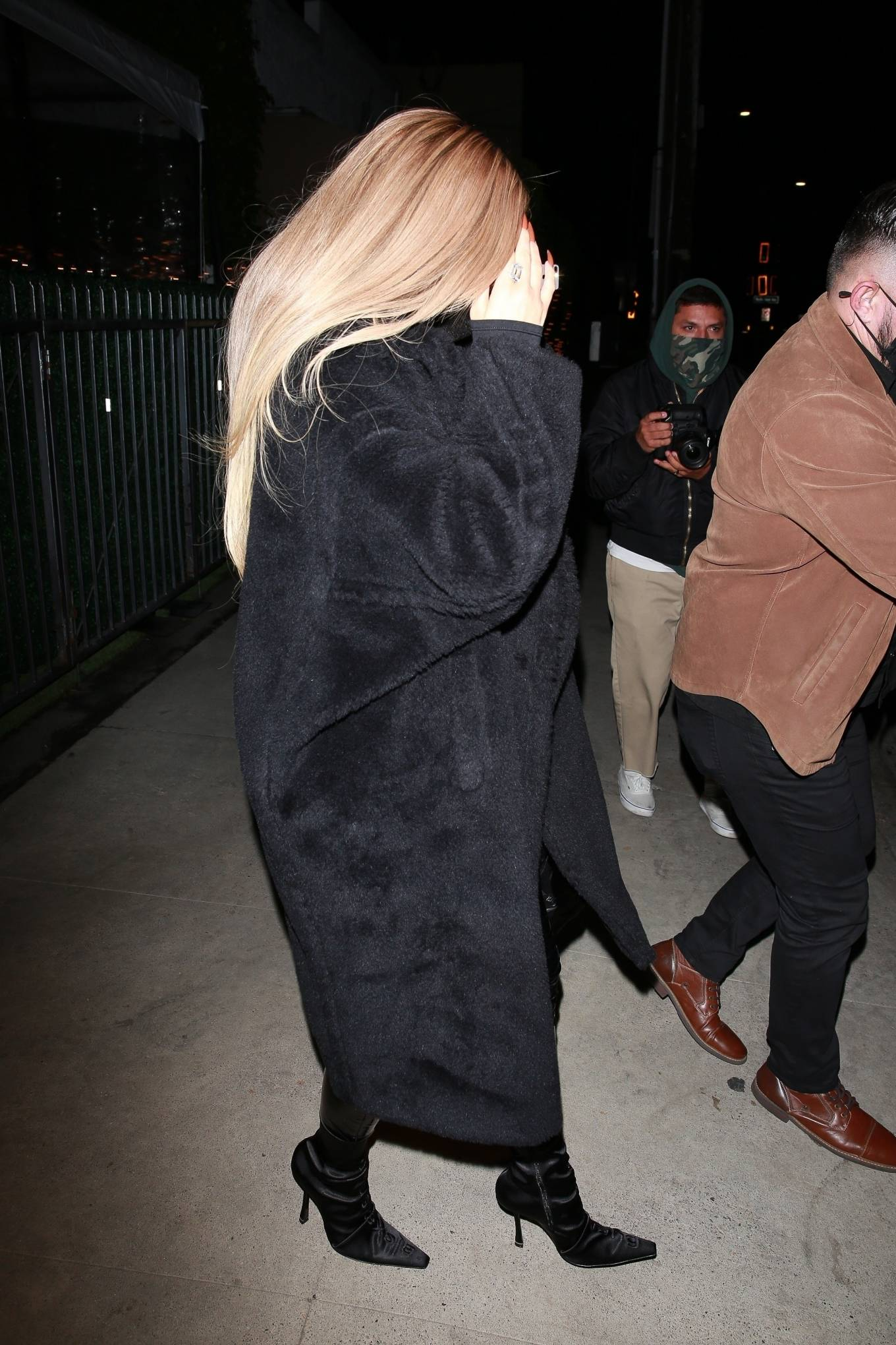 Kylie Jenner wearing a oversized black open front fur coat with extra long sleeves, drop shoulder and notched lapel collar