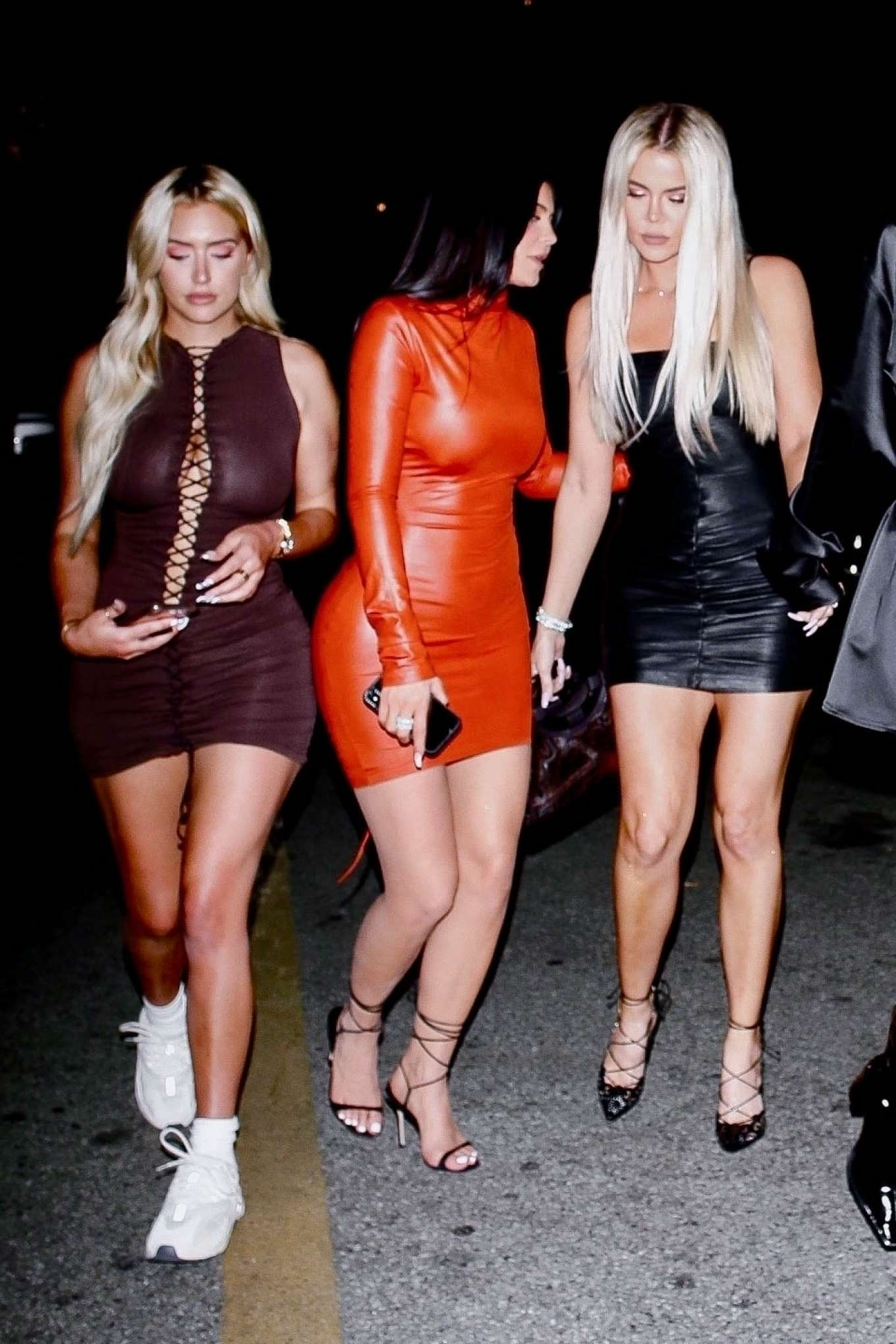 Kylie Jenner donning a Formfitting metallic red dress with a latex material, extra long sleeves, a turtleneck and cinched waist