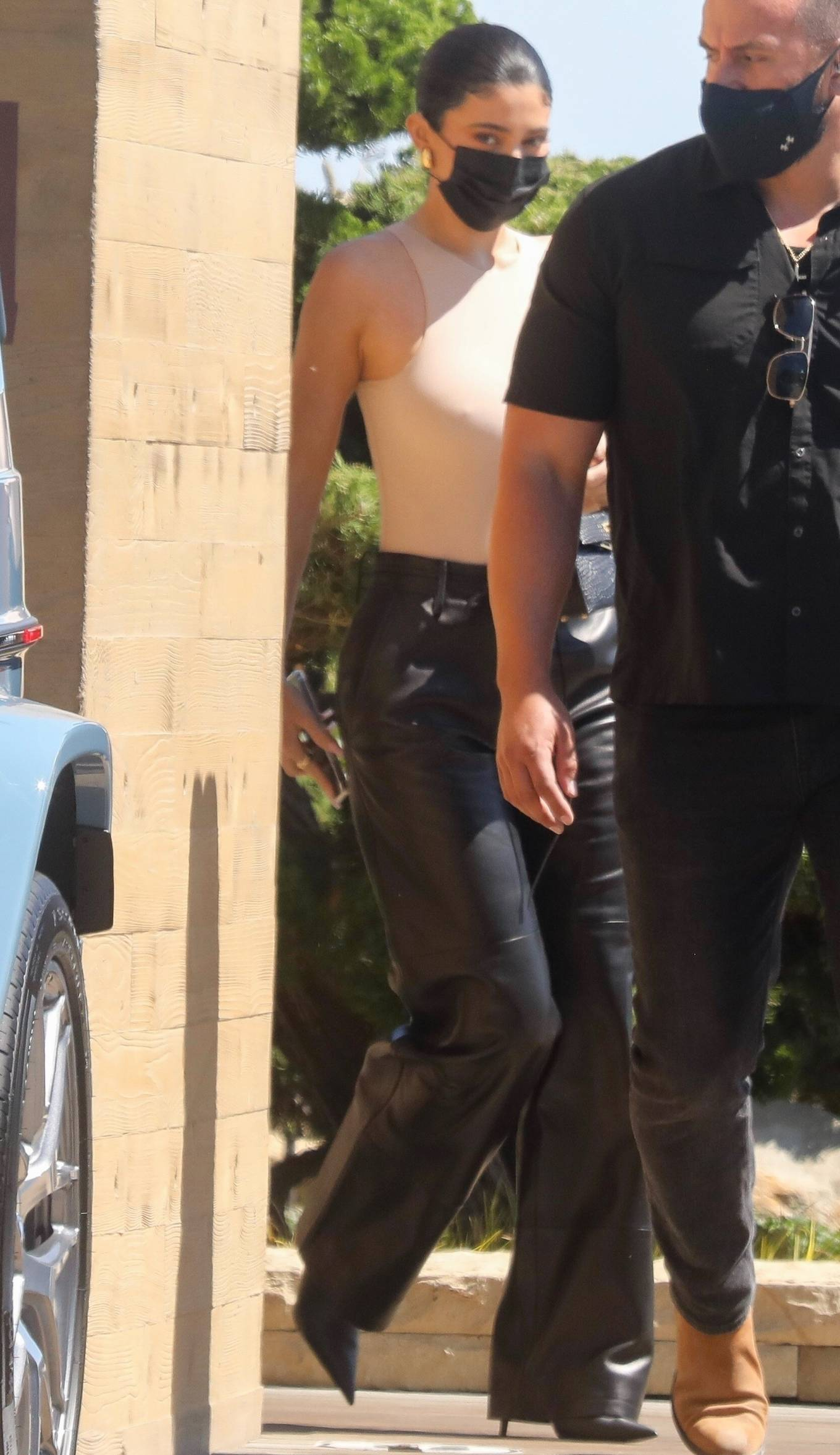Kylie Jenner donning straight fit black leather high rise flare trousers with side pockets