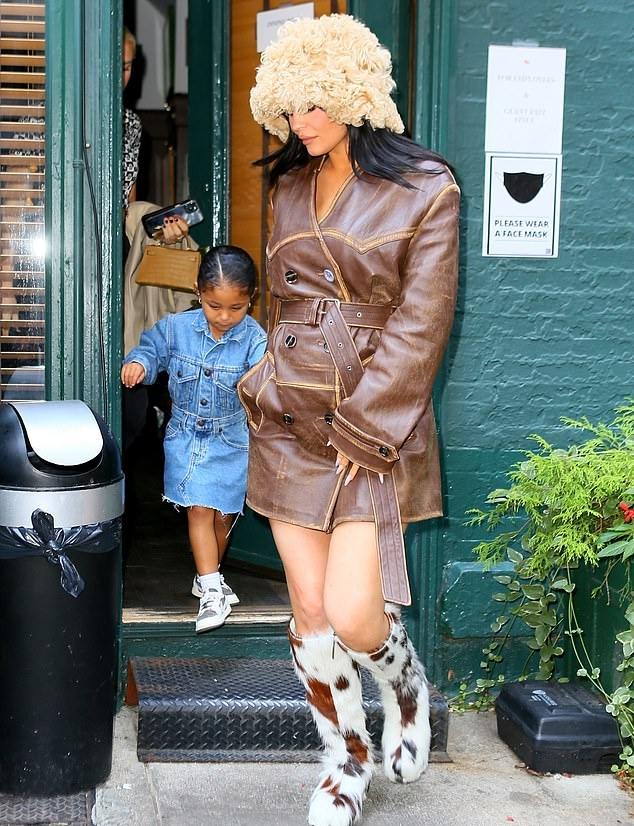 Kylie Jenner rocking round white faux fur knee high knee boots by Acne Studios with cow printed