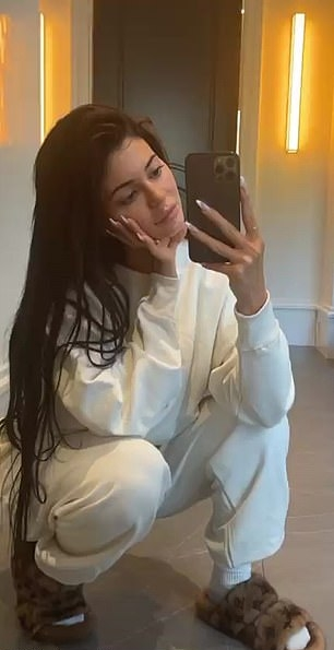Kylie Jenner, Louis Vuitton  mules, brown  mules, faux fur, oversized off white sweatshirt, flat heel, round, open toe, off white joggers, printed motifs, slip on, brand logo, two-strap