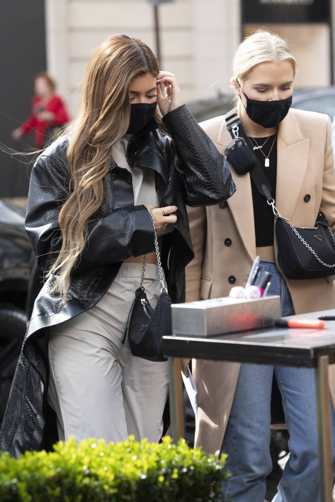 Kylie Jenner rocking a oversized black open front leather trench coat with a snakeskin material, extra long sleeves and peak lapel collar
