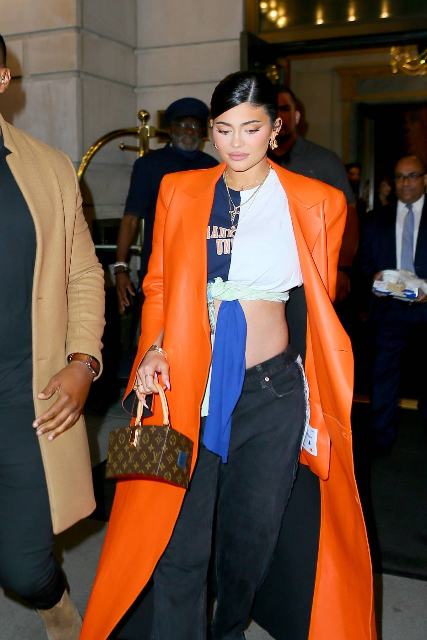 Kylie Jenner donning pointed orange slip on pumps by Off-White with block heel