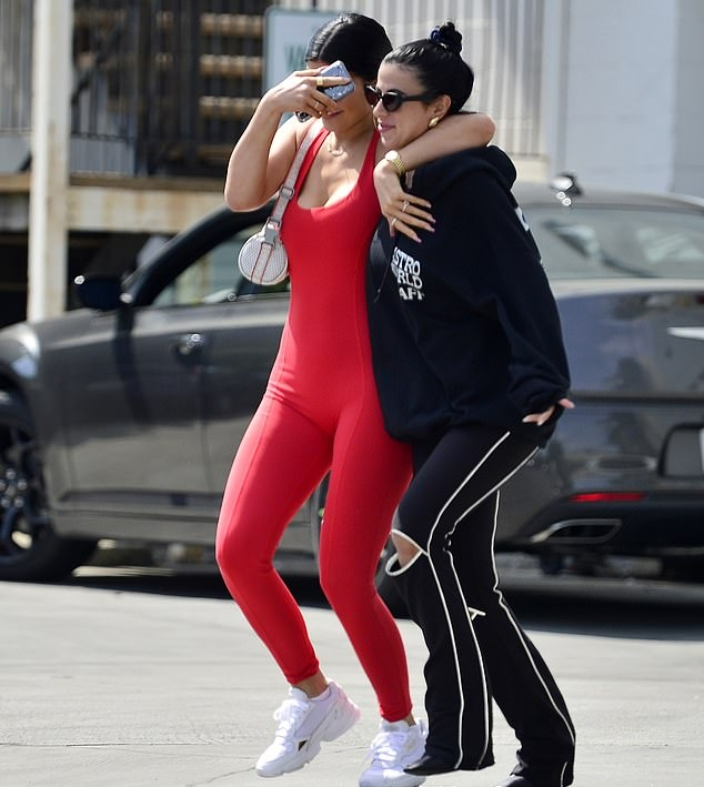 Kylie Jenner rocking a Figure hugging red jumpsuit with a polyester material, a scoop neck and straps