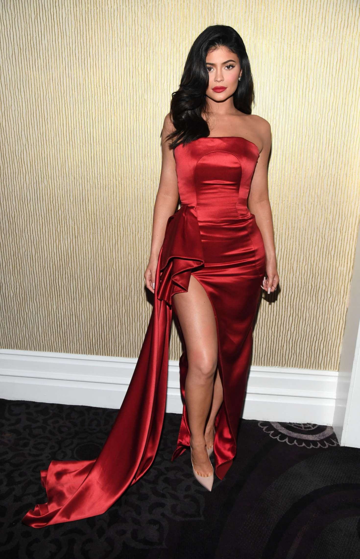 Kylie Jenner wearing a slinky shiny scarlet gown with a satin material and ruffled