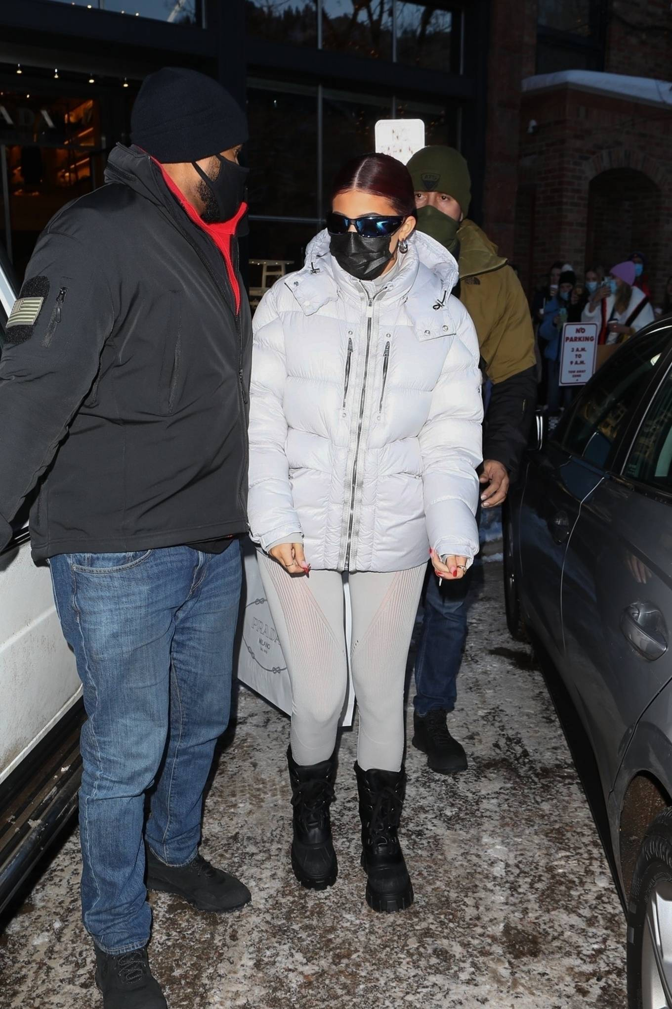 Kylie Jenner, grey pullover, nylon, Moncler pullover, oversized white Moncler jacket, black Prada winter boots, long sleeved, turtleneck, fitted, grey Moncler leggings. Kylie Jenner donning a fitted grey pullover with a nylon material, long sleeves, Half Zip closure at front and a turtleneck