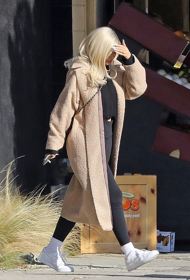 Kylie Jenner wearing a relaxed fit cream ankle length cashmere coat with a fleece fabric, extra long sleeves and notched lapel collar