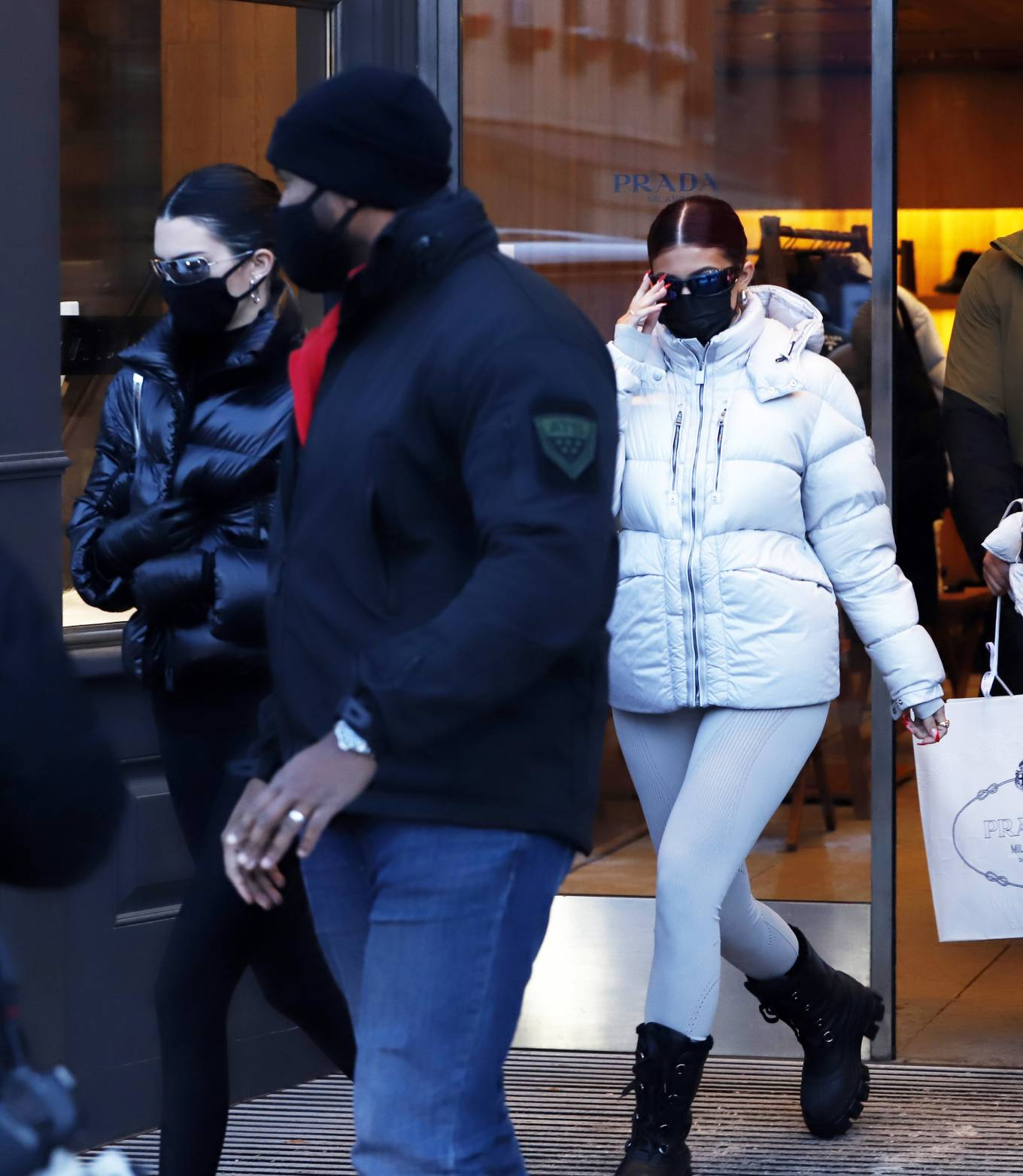 Kylie Jenner, Moncler pullover, grey pullover, nylon, oversized white Moncler jacket, black Prada winter boots, turtleneck, fitted, long sleeved, grey Moncler leggings. Kylie Jenner donning a fitted grey pullover with a nylon material, long sleeves, Half Zip closure at front and a turtleneck