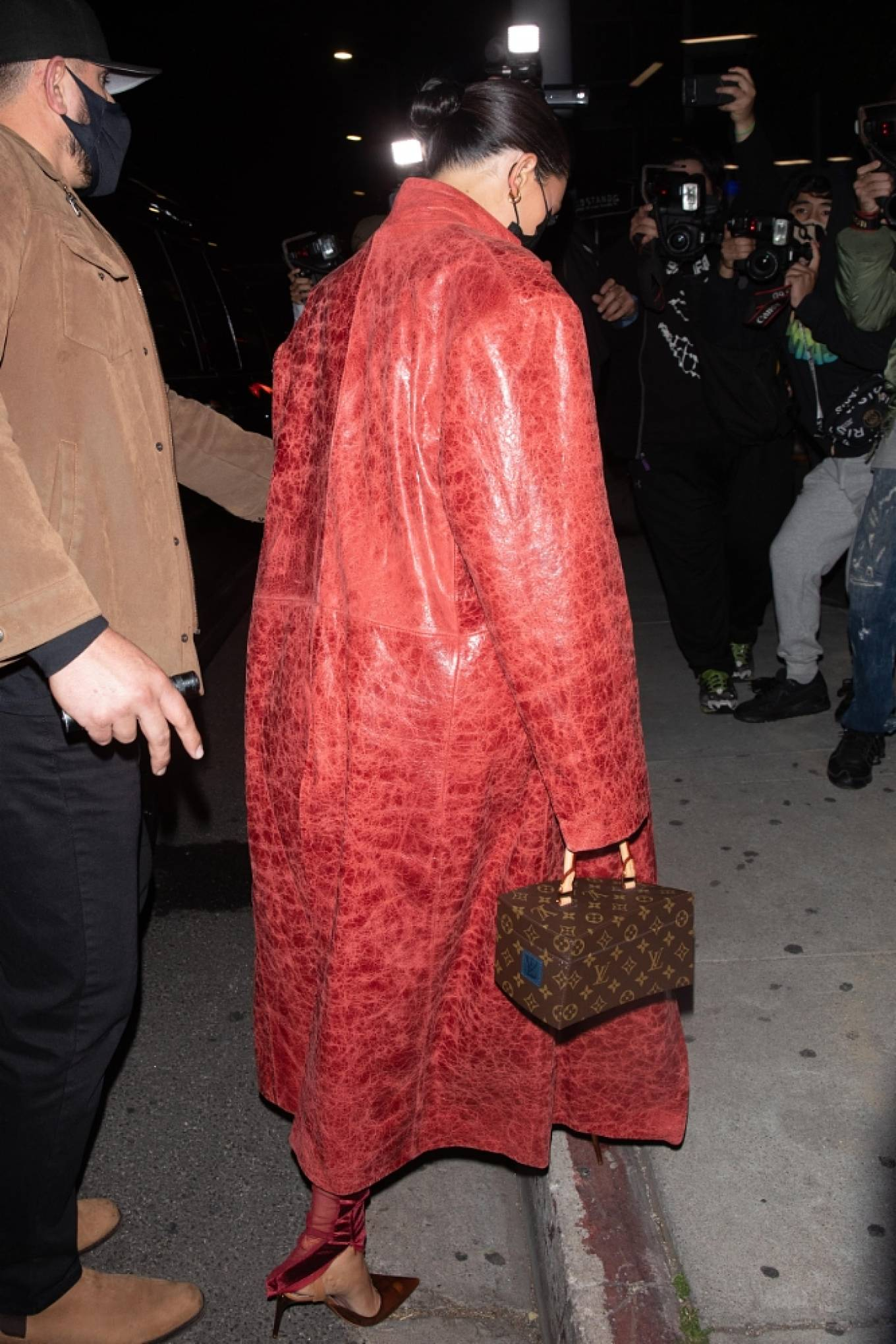 Kylie Jenner wearing a sheer catsuit with a velvet fabric, full sleeves, cut outs and a high neck