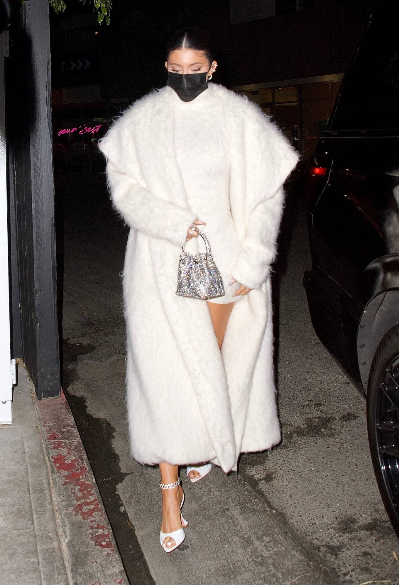 Kylie Jenner rocking a voluminous white hooded fur coat with a knit material, full sleeves and shawl collar
