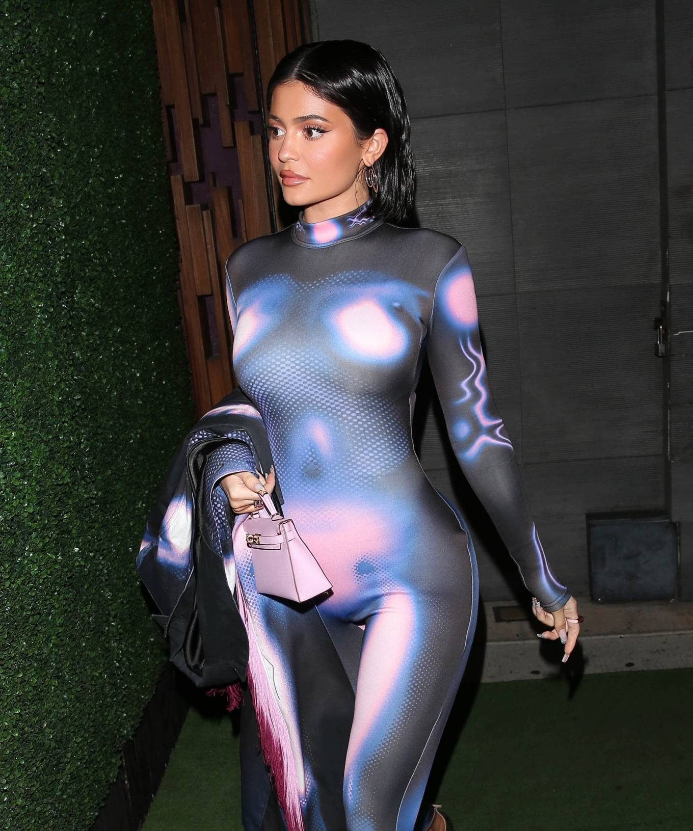 Kylie Jenner wearing a open front overcoat with full sleeves, lapel collar and Holographic print