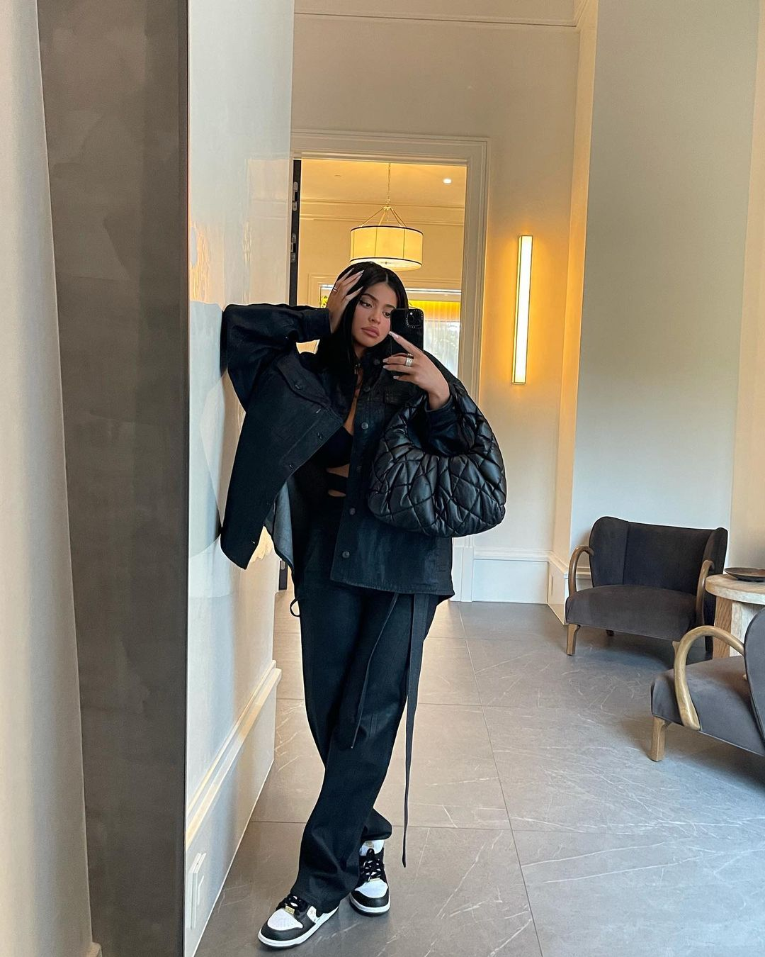 Kylie Jenner wearing brand logo black white lace-up sneakers by Nike with flat heel and printed motifs