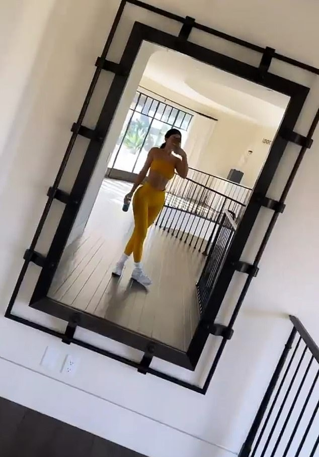 Kylie Jenner donning brand logo white Nike lace-up sneakers with flat heel