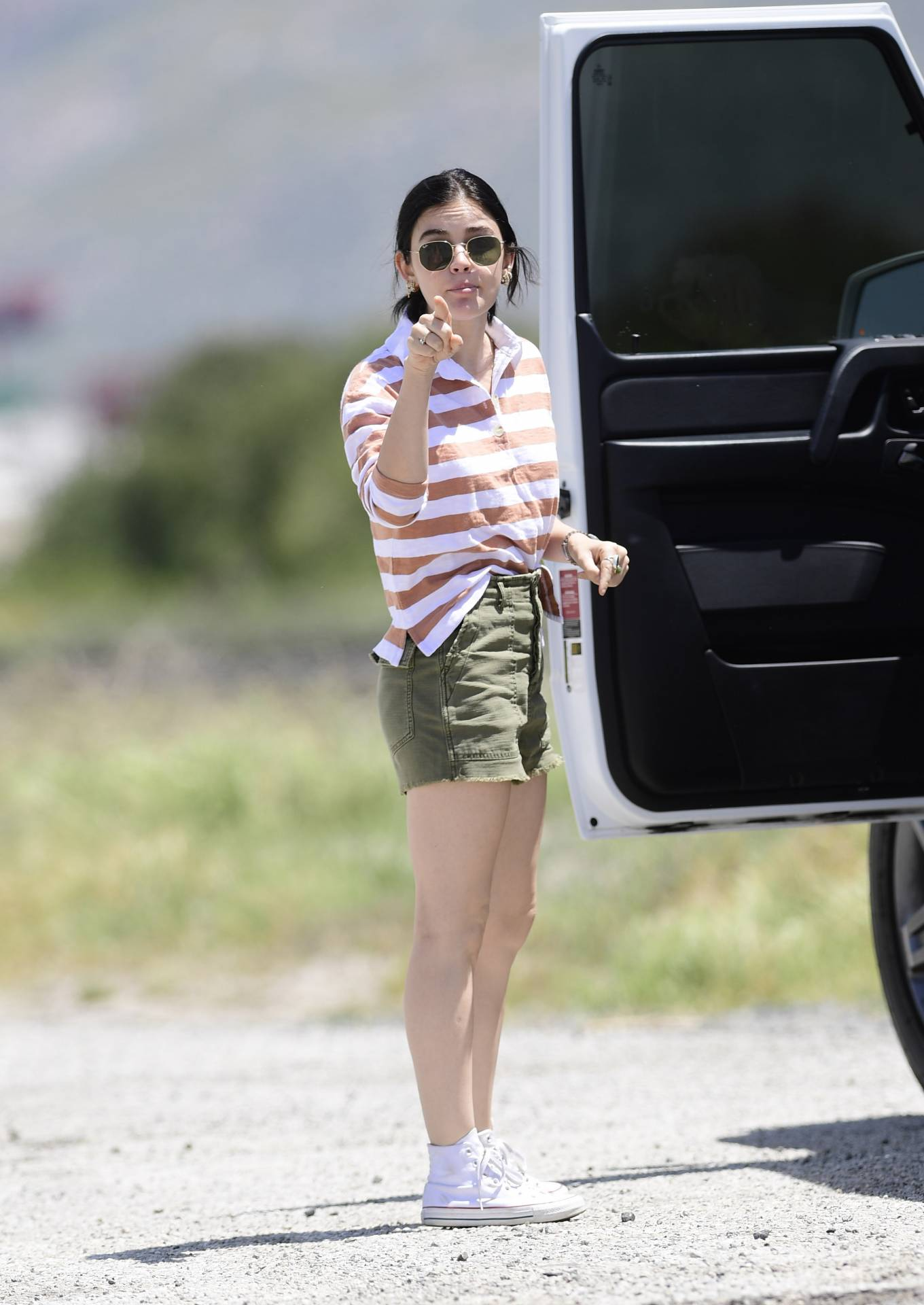 Lucy Hale, white  shirt, white Converse canvas shoes, button front, waist length, 3/4 sleeves, shirt collar, casual, black Ray Ban aviator, beige striped, tucked in