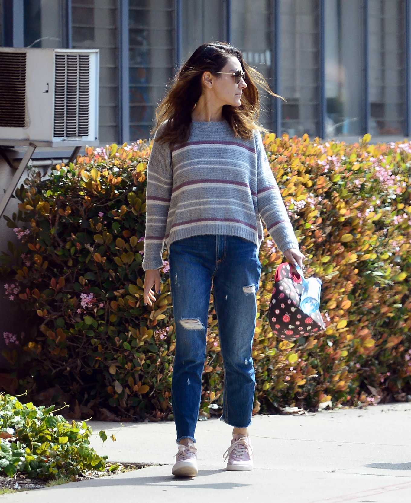 Mila Kunis donning a Grey woolen sweater with a woolen fabric, full sleeves, striped, a crew neck and ribbed trim hem