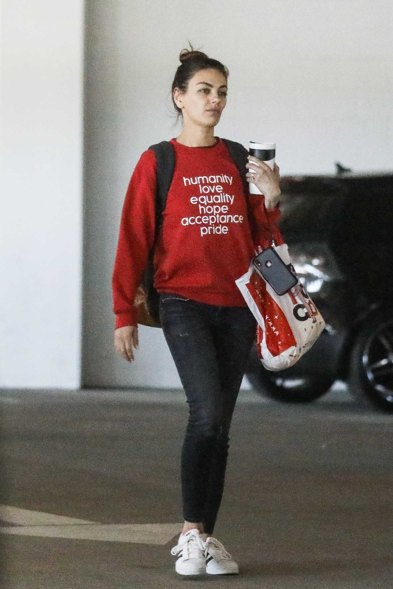 Mila Kunis wearing a Oversized slogan printed red sweatshirt with a woolen material, extra long sleeves, a crew neck and ribbed trim hem