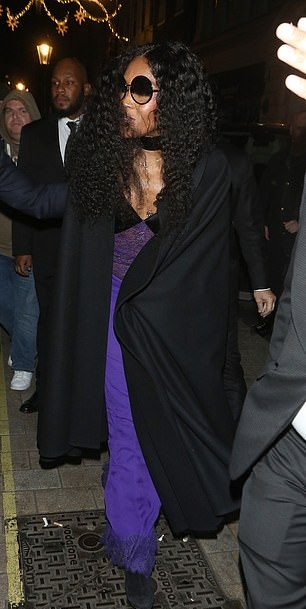 Naomi Campbell rocking narrow suede black knee high boots with high heel
