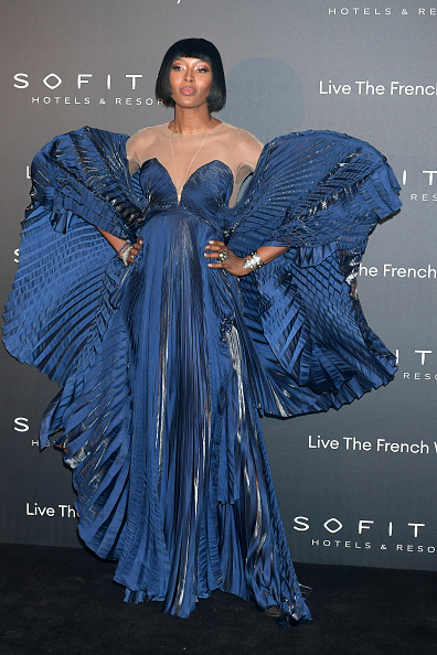 Naomi Campbell donning a oversized Royal blue gown with a fishnet fabric, flared sleeves, embellished, a very low cut sweetheart neckline and cinched waist