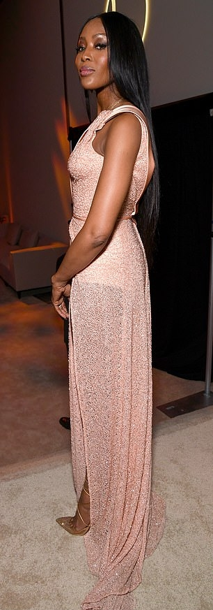 Naomi Campbell donning a Glittery pale pink Versace dress with a sequin detailing material, one shoulder, a asymetrical neckline, cinched waist and flared hem