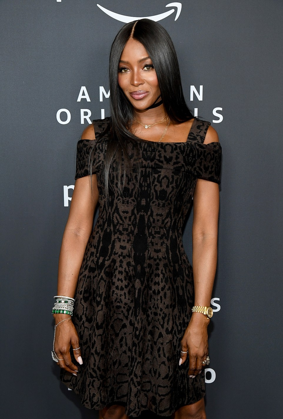 Naomi Campbell donning a Flare black dress with cap sleeves, cold shoulder and flared hem