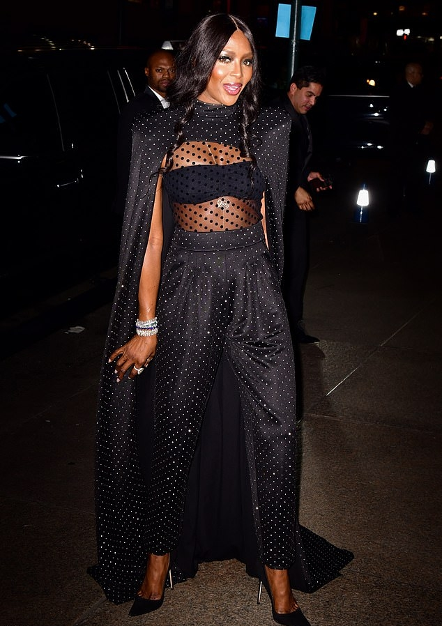 Naomi Campbell donning a Sheer glittery black jumpsuit with a sheer fabric, cape sleeves, pleated and a turtleneck
