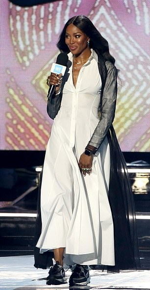 Naomi Campbell wearing a Flattering white dress with full sleeves, shirt collar, button front and flared hem
