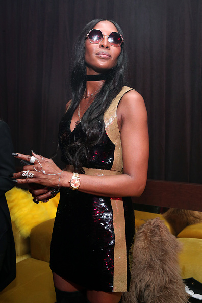 Naomi Campbell rocking a Plunging shiny black sequin mini dress with a sequin detailing fabric, side-stripes, a V-neck and straps